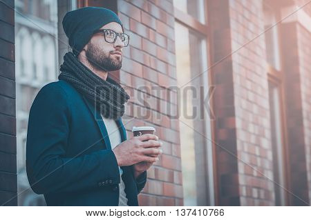 Enjoying city lifestyle. Handsome young man in smart casual wear holding coffee cup and looking away while standing at the street