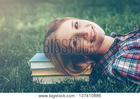 Enjoying her break. Beautiful young woman lying on the grass with head on the book stack