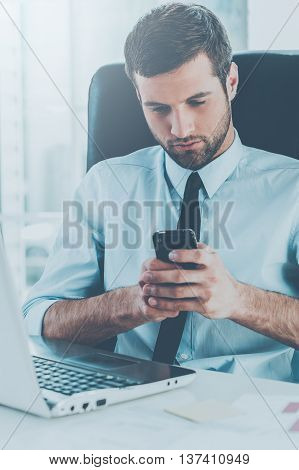 Typing quick message. Handsome young man in formalwear looking at his mobile phone while sitting at his working place