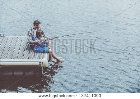 Fishing together. Top view of father and son fishing together while sitting on quayside
