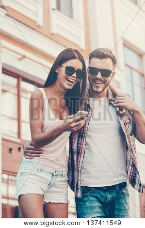 Look at this! Low angle view of beautiful young loving couple standing outdoors together and looking at the mobile phone