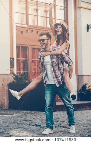 Carefree fun. Full length of happy young man carrying his beautiful girlfriend on shoulders and smiling while walking by the street