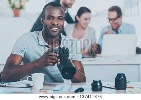 Confident photographer. Handsome young African man holding camera and smiling while three people working on background