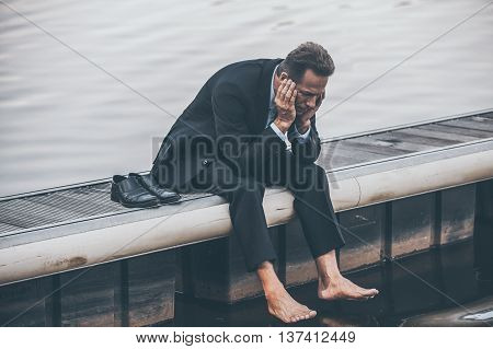 Depressed and hopeless. Depressed mature businessman holding head in hands while sitting barefoot at the quayside