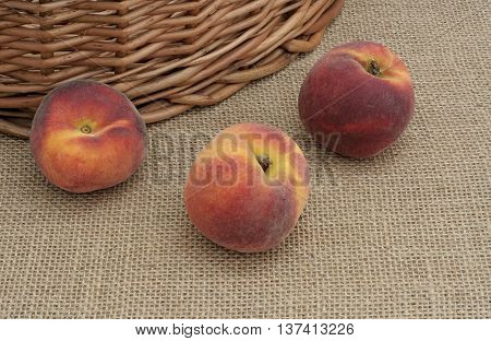 three peaches lying on the canvas at the basket