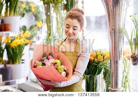 people, business, sale and floristry concept - happy smiling florist woman holding bunch of flowers wrapped into paper at flower shop