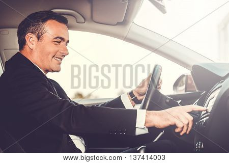 Driving with pleasure. Side view of cheerful mature man in formalwear driving car and touching dashboard with finger