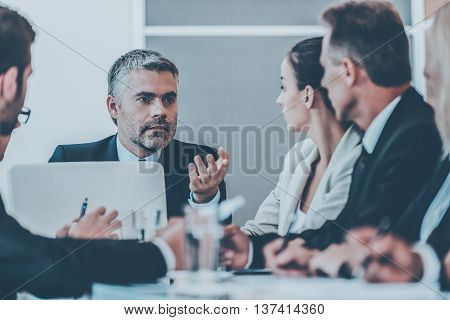 Discussing business. Business people in formalwear discussing something while sitting together at the table