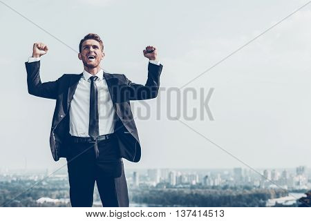 Used to win every day. Happy young man in formalwear keeping arms raised and expressing positivity while standing outdoors with cityscape in the background