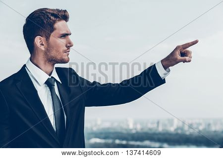 Pointing at opportunities. Confident young man in formalwear pointing away while standing outdoors with cityscape in the background
