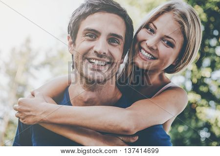 Happy loving couple. Low angle view of beautiful young loving couple standing outdoors together while woman hugging her boyfriend and smiling