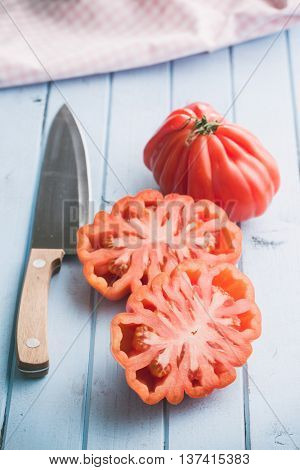 Coeur De Boeuf. Beefsteak tomatoes and knife on kitchen table.