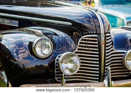 MINSK BELARUS - MAY 07 2016: Close-up photo of black Buick Eight 1940 model year. Old vintage car. Headlights of retro auto. Selective focus.