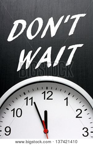 The words Don't Wait in white text on a blackboard above a modern wall clock with the time at almost midnight