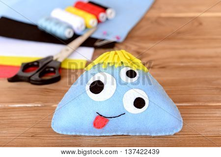 Stitched felt toy, threads kit, scissors, felt sheets on wooden background. Soft funny blue monster. Halloween sewing crafts idea for kids. Children toy project