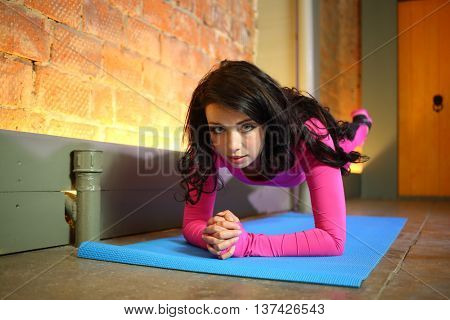 Beautiful woman in a pink tracksuit standing on elbows raises her feet up