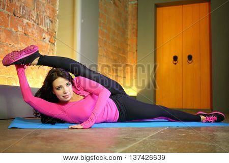 Beautiful woman in a pink tracksuit lying on side threw a leg over her head