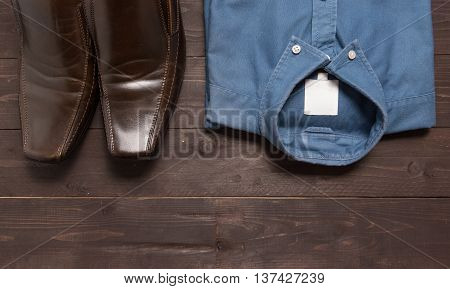 Shoes and menswear are on the wooden background.