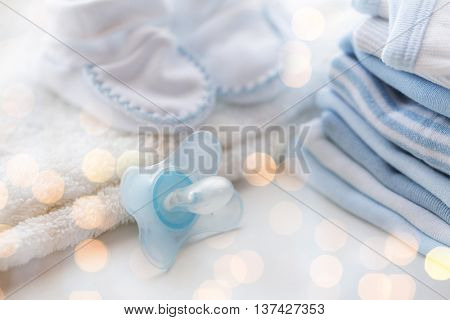 clothing, babyhood, motherhood and object concept - close up of baby soother, bootees and pile of clothes for newborn boy with holidays lights
