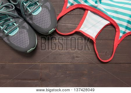 Sneakers and activewear are on the wooden background.