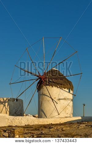 The last rays of the sun over White windmills on the island of Mykonos, Cyclades, Greece