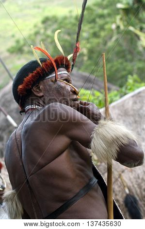 NEW GUINEA INDONESIA -DECEMBER 28: The warrior of a Papuan tribe in traditional clothes and coloring in New Guinea Island Indonesia on December 28 2010