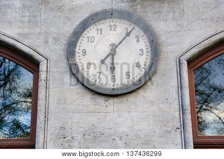 Old clock on the gray wall outdoor