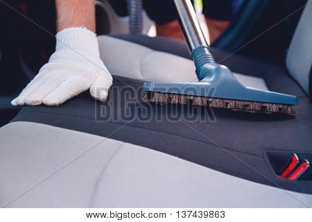 A man cleans the interior of the car. Vacuum cleaning car seats