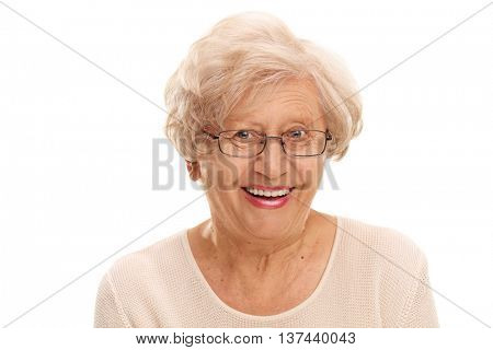 Close-up on a joyful senior lady smiling and looking at the camera isolated on white background