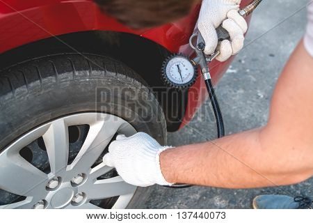 Pumping car tires in the service station. People at work. The man inflates car tires