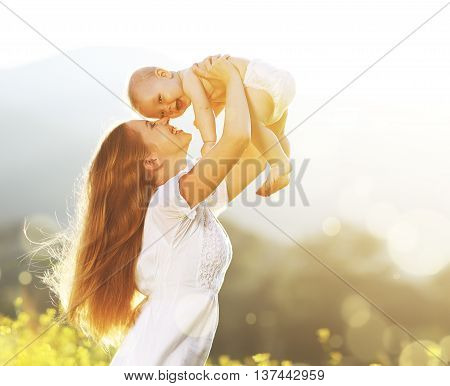 happy harmonious family outdoors. mother throws baby up laughing and playing in the summer on the nature