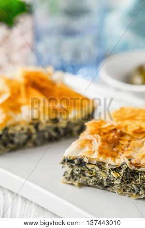 Greek pie spanakopita on the white plate with blurred accessorizes
