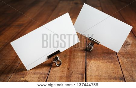 Photo of blank business cards on vintage wood table background. Mock up for ID. Blank template for branding identity for designers.
