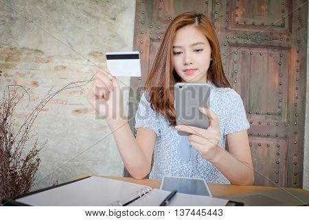 Photo of a beautiful young female shopping online and paying with a credit card. Credit card information is fictitious.