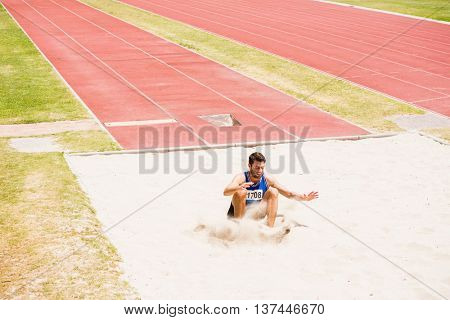Athlete landing on sandpit after performing a long jump