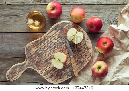 apples on a cutting board and glass of juice flat lay