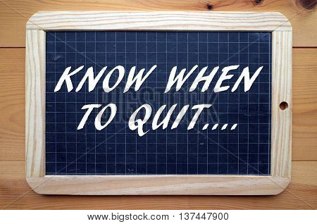The words Know When To Quit in white text on a blackboard as a reminder to change direction or have an exit strategy