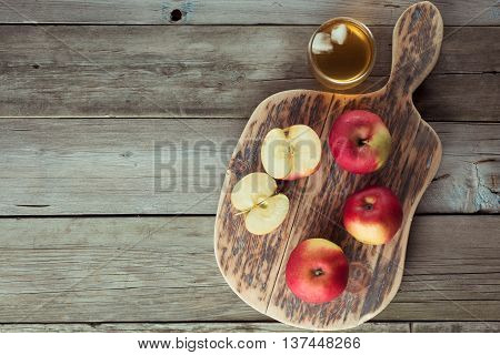 apples on a cutting board and glass of juice copyspace
