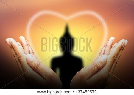 human hands Protect silhouette of Buddha with sun shining from behind.