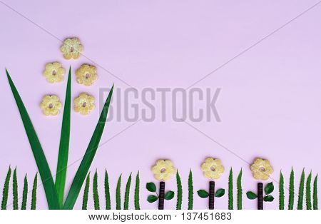 The composition of the single flower of the three green leaves and five biscuits chocolate and three daisies on green grass fern leaves