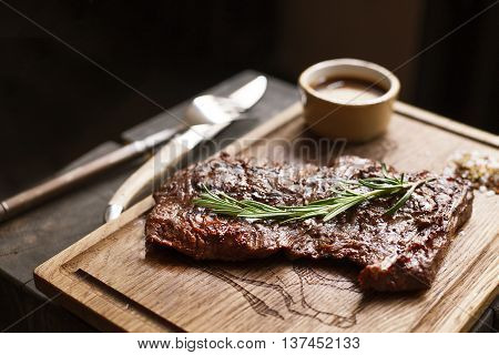 Beef steak. Piece of  Grilled BBQ beef marinated in spices and herbs on a rustic wooden board over rough wooden desk with a copy space. Top view