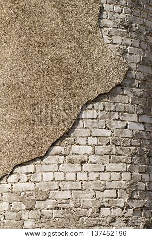 The bricks white and a piece of crumbling plaster. Exterior wall coating.