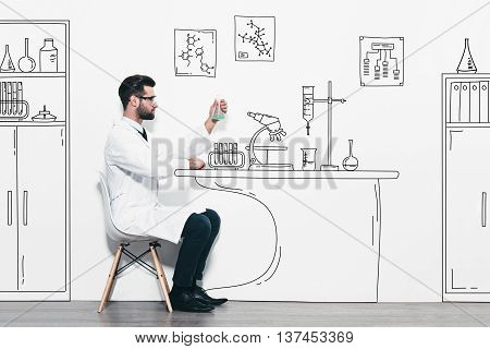 Scientific experiment. Confident young man in white uniform sitting against a wall and making scientific experiment in pencil drawn laboratory