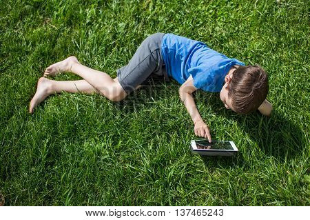 child is lying on the grass with tablet. boy playing with a digital tablet or watching a movie or listening to music outdoors. view from above