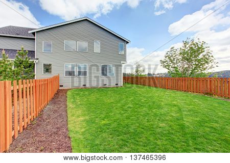 Spacious Fenced Back Yard With Green Grass. House Exterior Of A Large House.