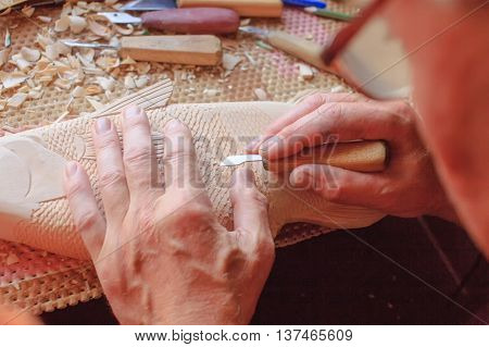 master carves wooden fish. woodcarving closeup. carpentry poster