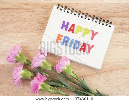 Word spell Happy Friday on notebook and bouquet of sweet pink Carnation flower on wood background with top view