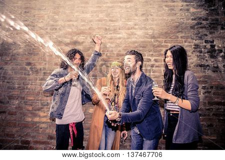 Group of friends uncorking champagne bottle in a nightclub