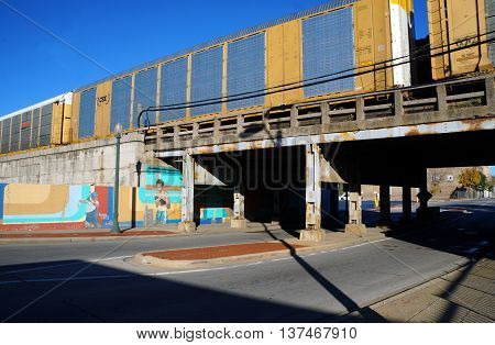JOLIET, ILLINOIS / UNITED STATES - NOVEMBER 1, 2015: A freight train crosses a bridge over Cass Street in downtown Joliet.