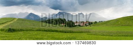 The village in the Alpine valleys and mountains in the mist on the horizon in the south of Bavaria, Germany